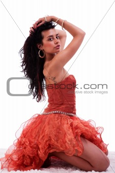 Beautiful woman on floor with hands holding the hair, looking to camera, on white, studio shot