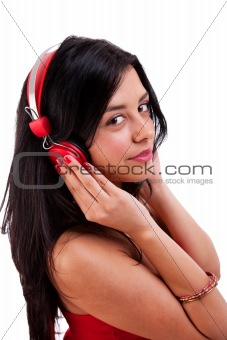 beautiful woman standing listening to music on red headphones, isolated on white, studio shot
