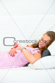 Beautiful woman lying on couch and looking at clock