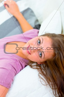Portrait of smiling young woman lying on white couch
