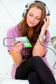 Attractive woman sitting on couch and listening music in headphones