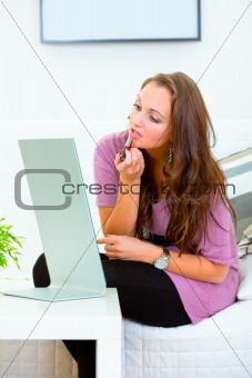 Charming woman sitting in front of mirror and applying lipstick