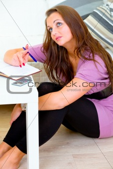 Thoughtful woman sitting on floor and making notes in diary