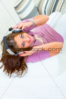 Cheerful young woman sitting on sofa and listening music in headphones
