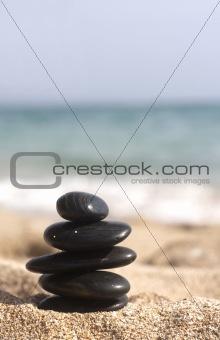 five black stones pyramid on the sandy beach