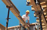 Construction worker placing formwork beams