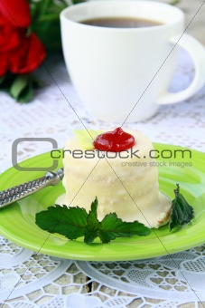 small cake on a plate with a cup of coffee elegant still life