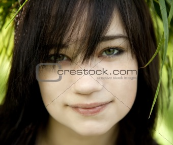 Portrait of brunette teen girl at green outdoor.