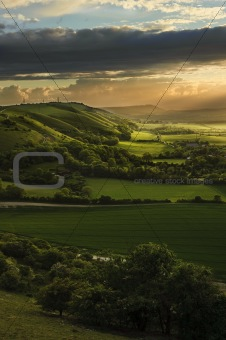 Stunning Summer sunset over countryside escarpment landscape