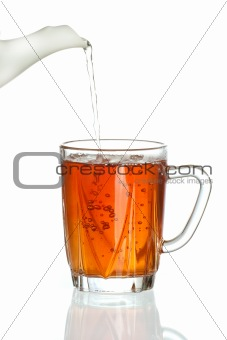 Pouring tea into transparent tea cup