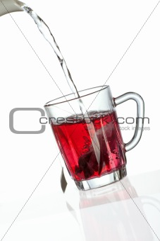 Pouring tea into transparent tea cup