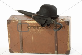 Old suitcase, bowler hat and umbrella