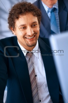 Young smiling businessman working on laptop