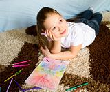 The girl lies on a carpet and thoughtfully draws