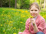 The beautiful girl smells a dandelion on a green field