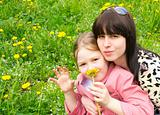 Mother and the daughter on a green meadow with dandelions