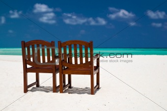 pair of chairs on a tropical beach