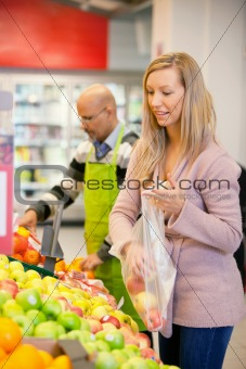 Young woman buying fruits