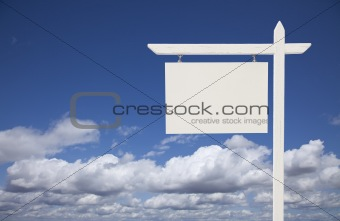 Blank White Real Estate Sign Over Clouds and Sky Ready For Your Own Message.