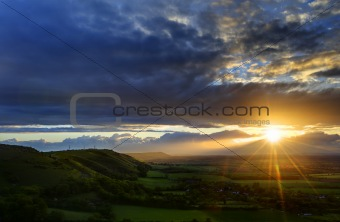 Beautiful landscape across countryside with sun beams lighting hills