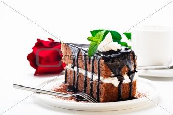 A piece of chocolate cake with vanilla cream and a rose