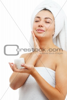 Beautiful women applying moisturizer cosmetic cream on face.