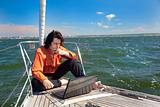 Businessman with laptop on sailboat