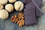 walnuts and dark chocolate on a wooden background
