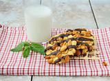 homemade cookies with chocolate and nuts and a glass of milk