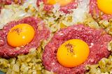 tartar steak with egg onion and pickle