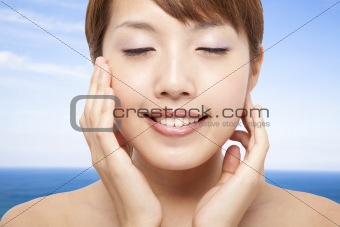 Beautiful Woman Face closeup and blue ocean background