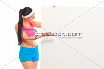 Fit girl in sportswear looking and pointing on blank billboard
