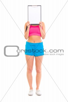 Fitness girl holding blank clipboard in front of her face
