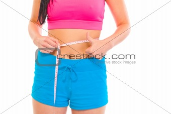 Fitness girl measuring her waist and showing thumbs up gesture. Close-up.