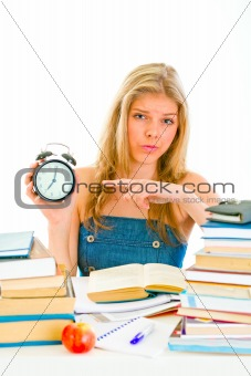 Worried teengirl sitting at table with books and pointing finger on alarm clock