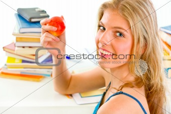 Smiling teen girl sitting at desk with books and holding apple in hand