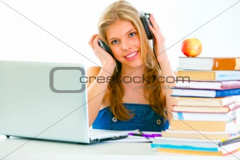 Sitting at table smiling teengirl with headphone listening audio lessons