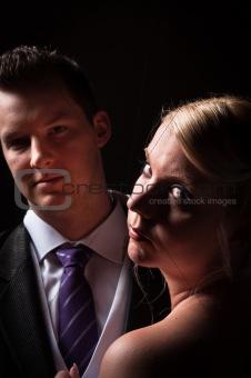 Groom and bride against dark background