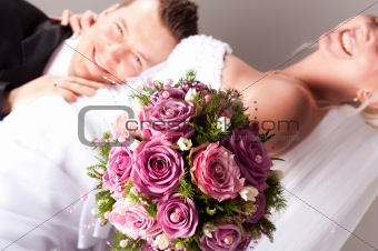 young couple in wedding wear with bouquet of roses