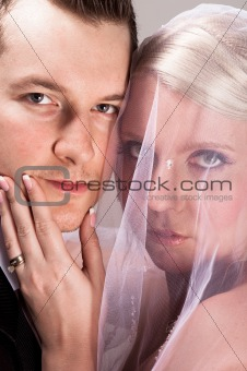 Young bride in veil holding the chin of the groom
