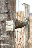 Wooden fence with metal plate against blurry background