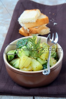 potato salad with cucumber and dill on a brown background