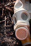 A gasmask on burnt ground