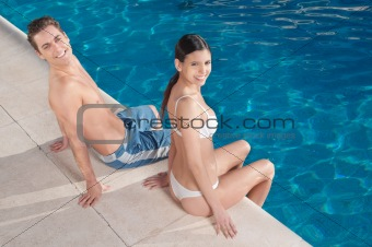 Young couple relaxing by the poolside