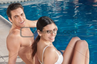 Beautiful young couple relaxing by the poolside