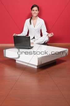 Beautiful businesswoman sitting in yoga lotus position