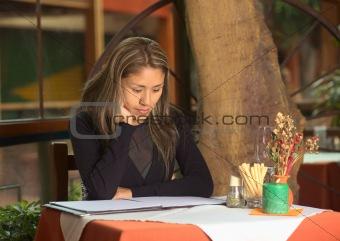 Beautiful Young Peruvian Woman Looking at a Menu