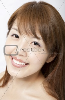 smiling beautiful asian woman's face with fresh clean skin