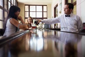 women drinking cocktail in pub