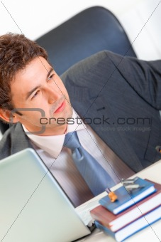 Alert modern businessman sitting at office desk  and looking in corner. Close-up